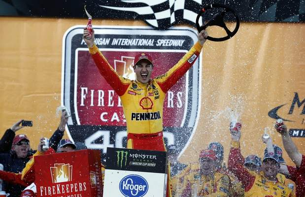 Associated Press photos Joey Logano celebrates his second NASCAR Cup victory of the season Monday after prevailing in overtime  at Michigan International Speedway in Brooklyn, Mich.