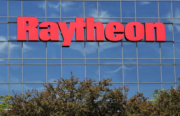 The sky is reflected on the facade of Raytheon's facility in Woburn, Mass., on Monday, the day after an announced merger with United Technologies Corp.