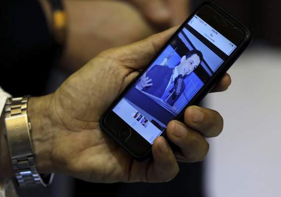 FILE - In this July 18, 2017 file photo, Ziad Zakka, brother of Nizar Zakka who is imprisoned in Iran, shows a photo of his brother on his cellular telephone in Beirut, Lebanon. (AP Photo/Bilal Hussein, File)