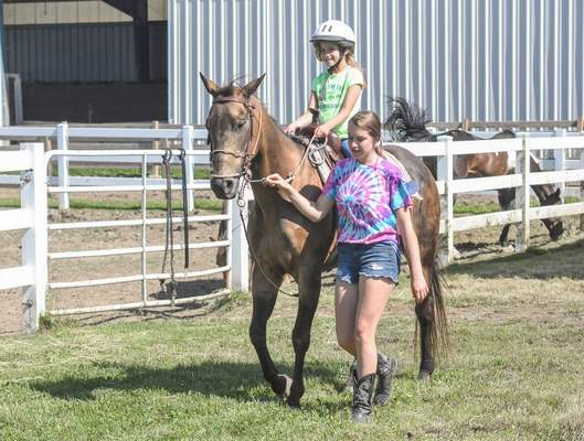 Michelle Davies | The Journal Gazette Samantha Conrad, 17, leads camper Katerine Laubhan, 8, on her quarter horse Candy at Tuesday's S&B Horse Camp at Blue Willow Farm. The camp is designed to help participants learn  about horses, caring for them, including grooming, safety and riding. as well as outdoor activities and crafts.