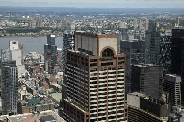 Law enforcement personnel work on the roof of the AXA Equitable building, center, Tuesday, June 11, 2019 in New York. (AP Photo/Mark Lennihan)