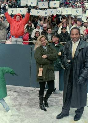 FILE - In this Nov 25, 1993, file photo, O.J. Simpson stands with Nicole Brown Simpson while broadcasting on the sidelines during the Thanksgiving Day NFL football game in Irving, Texas. (AP Photo/Ron Heflin, File)