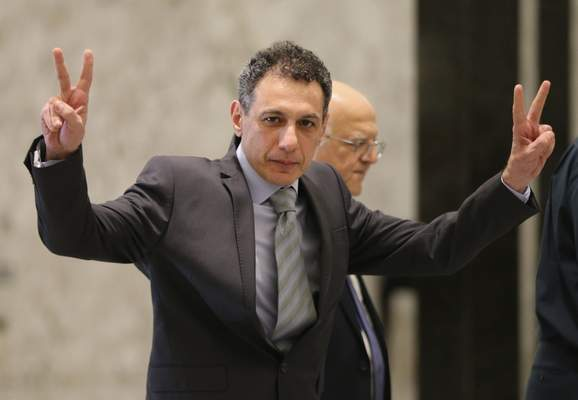 Nizar Zakka, a Lebanese citizen and U.S. permanent resident, who was released in Tehran after nearly four years in jail on charges of spying, flashes victory signs upon his arrival at the presidential palace, in Baabda, east of Beirut, Tuesday, June 11, 2019. (AP Photo/Hussein Malla)