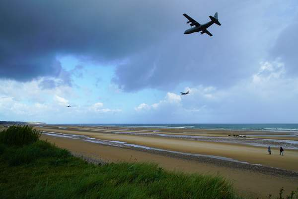 Three vintage World War II aircraft fly low over Omaha Beach in Colleville-sur-Mer, France, on Saturday, June 8, 2019. (AP Photo/Allen G. Breed)