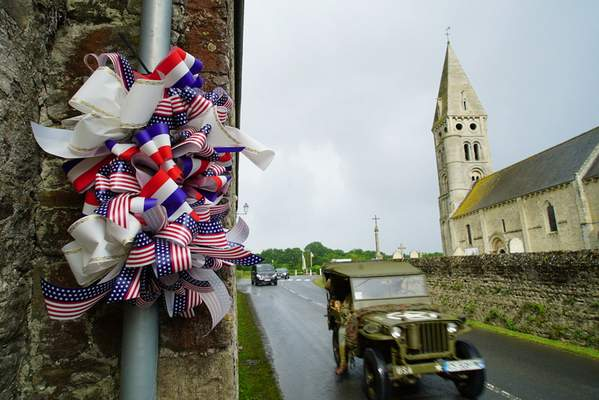 A vintage World War II jeep passes by a decoration along the main road in Colleville-sur-Mer, France, on Saturday, June 8, 2019. (AP Photo/Allen G. Breed)