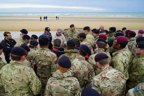Members of the 12th Regiment, Royal Artillery, gather around to listen in as D-Day survivor Ray Lambert shares war stories on Omaha Beach in Colleville-sur-Mer, France, on Friday, June 7, 2019. (AP Photo/Allen G. Breed)