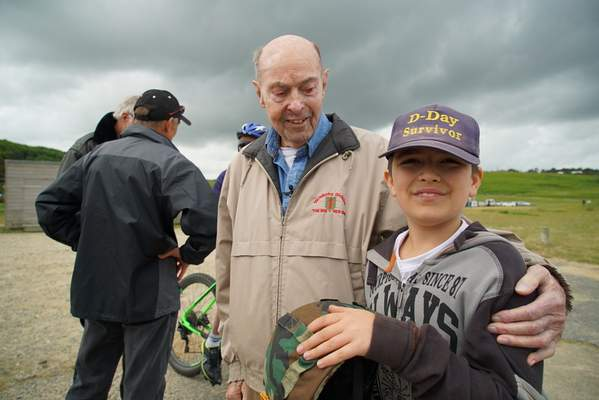 D-Day veteran Ray Lambert shares his lucky hat with a young Italian tourist at Omaha Beach in Colleville-sur-Mer, France, on Wednesday, June 5, 2019. (AP Photo/Allen G. Breed)