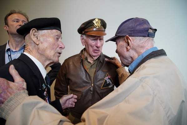 D-Day survivor Ray Lambert, right, talks with fellow World War II veterans Roy O'Neill of Great Britain, left, and Jim Kunkel of California during a reception at the Overlord Museum in Colleville-sur-Mer, France, on Friday, June 7, 2019. (AP Photo/Allen G. Breed)