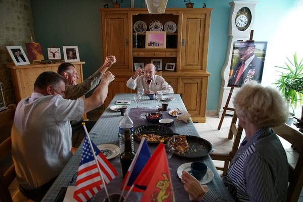 Christophe Coquel, left, Darrell Simpkins and Coquet's wife, Chantal, raise glasses of calvados brandy to toast D-Day veteran Ray Lambert at the Coquel home in Le Douet de Chouain, France, on Saturday, June 8, 2019. (AP Photo/Allen G. Breed)
