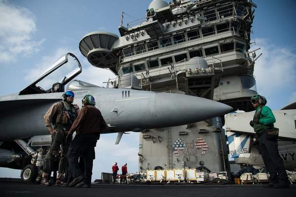 FILE - In this June 3, 2019 file photo, a pilot speaks to a crew member by an F/A-18 fighter jet on the deck of the USS Abraham Lincoln aircraft carrier in the Arabian Sea. (AP Photo/Jon Gambrell, File)