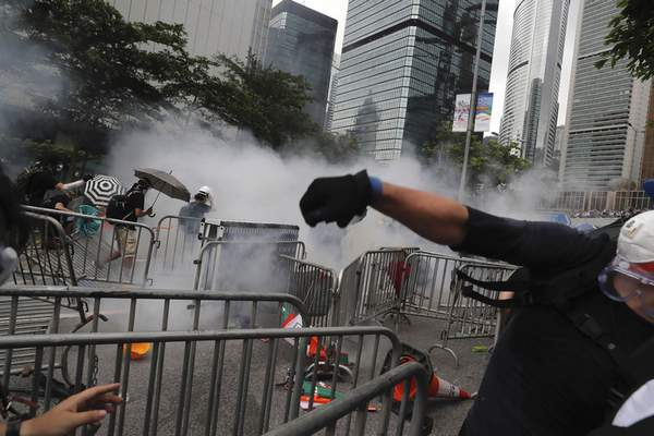 Protesters react to tear gas during a massive protest near the Legislative Council in Hong Kong, Wednesday, June 12, 2019. (AP Photo/Kin Cheung)