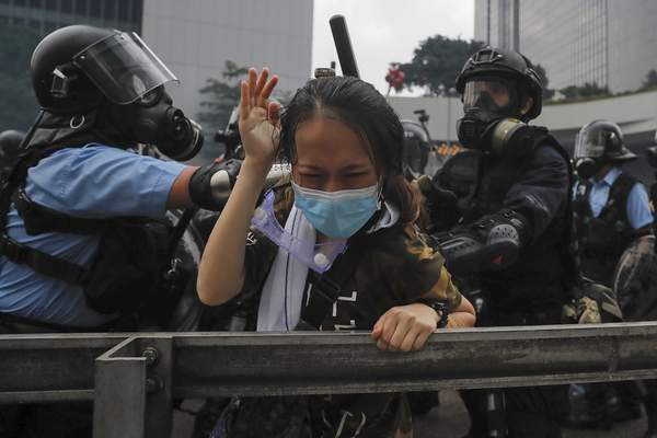 A protester reacts as she tackled by riot police during a massive demonstration outside the Legislative Council in Hong Kong, Wednesday, June 12, 2019. (AP Photo/Kin Cheung)