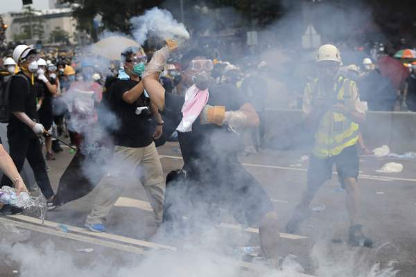 A demonstrator throws a canister of tear gas back towards the police outside the Legislative Council in Hong Kong, Wednesday, June 12, 2019. (AP Photo/Kin Cheung)