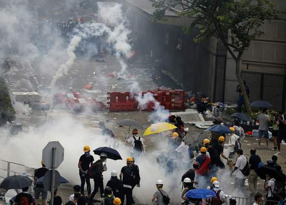 Riot police fire tear gas to protesters outside the Legislative Council in Hong Kong, Wednesday, June 12, 2019. (AP Photo/Vincent Yu)
