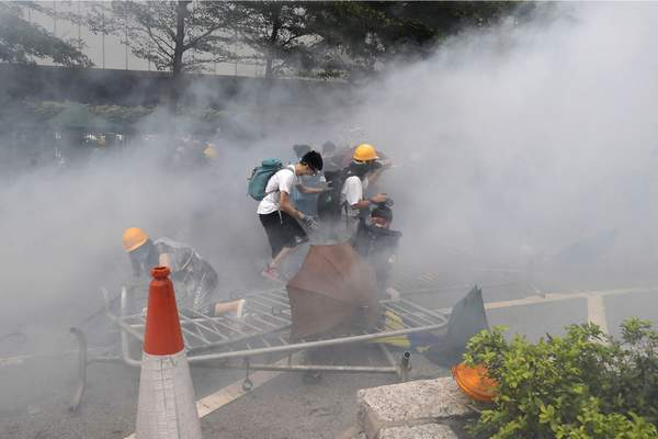 Protesters react to a cloud of tear gas near the Legislative Council in Hong Kong, Wednesday, June 12, 2019. (AP Photo/Kin Cheung)
