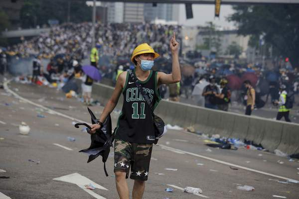 A protester gestures after clashes with riot police during a massive demonstration outside the Legislative Council in Hong Kong, Wednesday, June 12, 2019. (AP Photo/Kin Cheung)