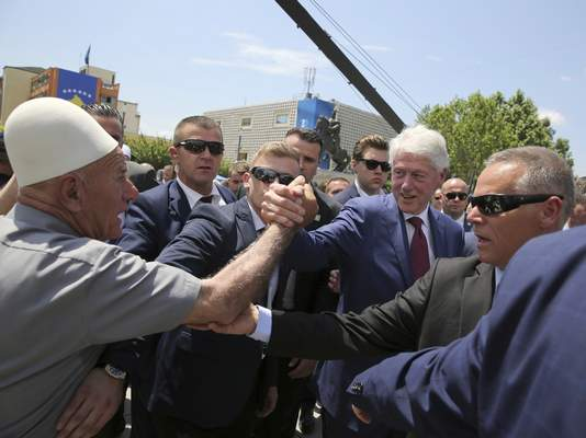 Former U.S. President Bill Clinton, center right, shakes hands with an elderly ethnic Albanian wears his traditional cap during anniversary celebrations in the capital Pristina, Kosovo, Wednesday, June 12, 2019. (AP Photo/Visar Kryeziu)