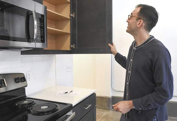 Caleb Young checks out the cabinet space in his new studio apartment in The Landing on Wednesday morning after being the first resident to sign a lease. The $32.6million development on Columbia Street includes 70 apartments and 56,000 square feet of commercial and retail space.