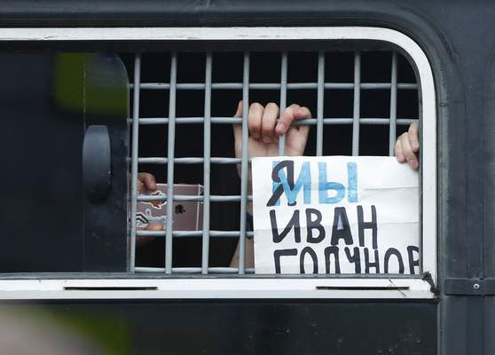 A detained supporter of Russian investigative journalist Ivan Golunov shows placard reading