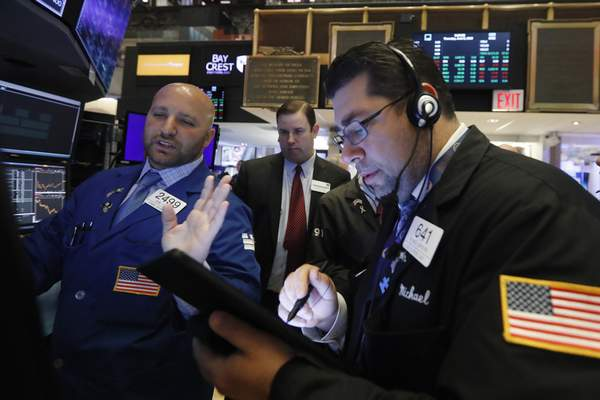 FILE- In this June 6, 2019, file photo specialist John Parisi, left, works with traders on the floor of the New York Stock Exchange. (AP Photo/Richard Drew, File)