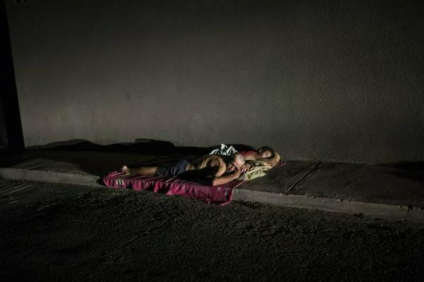 In this May 15, 2019 photo, people sleep on the sidewalk to escape from the heat, due to the lack of electricity in their homes that does not allow them to run their air conditioners and fans, during a blackout in Maracaibo, Venezuela. (AP Photo/Rodrigo Abd)