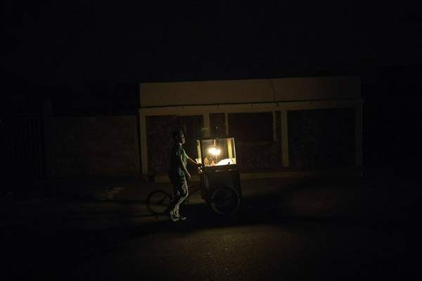 In this May 15, 2019 photo, popcorn vendor Raul Navas looks for customers during a black out in Maracaibo, Venezuela. Navas uses a kerosene lamp to illuminate his cart as he walks the streets during the blackout. (AP Photo/Rodrigo Abd)