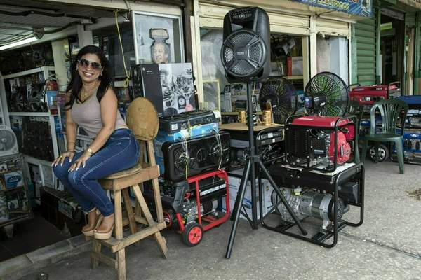 In this May 23, 2019 photo, power generator vendor Juli Barbosa poses for a photo while waiting for customers at the Maracaibo flea market, in Venezuela. (AP Photo/Rodrigo Abd)