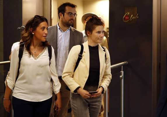 Amanda Knox, right, exits the airport from a side entrance upon her arrival in Linate airport, Milan, Italy, Thursday, June 13, 2019. (AP Photo/Antonio Calanni)