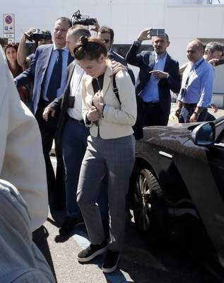 Amanda Knox is approached by a journalist upon her arrival in Linate airport, Milan, Italy, Thursday, June 13, 2019. (AP Photo/Antonio Calanni)