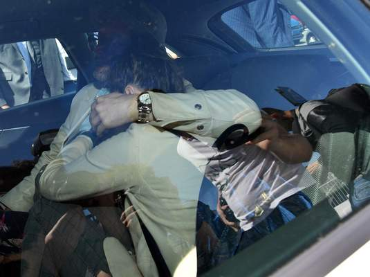 Amanda Knox hides her face from the cameras as she sits in a car after her arrival in Linate airport, Milan, Italy, Thursday, June 13, 2019. (Daniel Dal Zennaro/ANSA via AP)