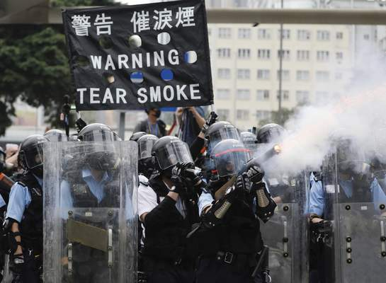 FILE - In this file photo taken Wednesday, June 12, 2019, police fire tear gas towards protesters outside the Legislative Council in Hong Kong. (AP Photo/Vincent Yu, File)