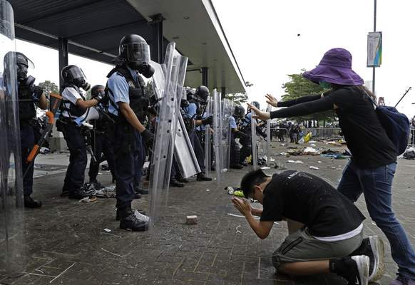 FILE - In this file photo taken Wednesday, June 12, 2019, a protester bows to riot police after they fire tear gas towards protesters outside the Legislative Council in Hong Kong. (AP Photo/Vincent Yu, File)