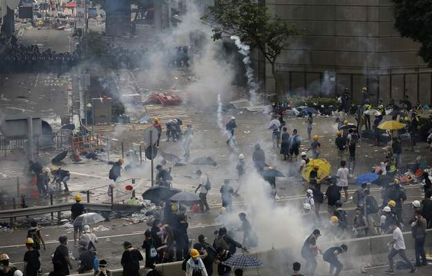 FILE - In this file photo taken Wednesday, June 12, 2019, riot police try to disperse protesters with fire tear gas outside the Legislative Council in Hong Kong. (AP Photo/Vincent Yu, File)