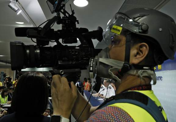 A press cameraman wears a helmet for protection in the clashes seen in recent protests, films a press conference by Commissioner of Police Stephen Lo in Hong Kong, Thursday, June 13, 2019. (AP Photo/Vincent Yu)