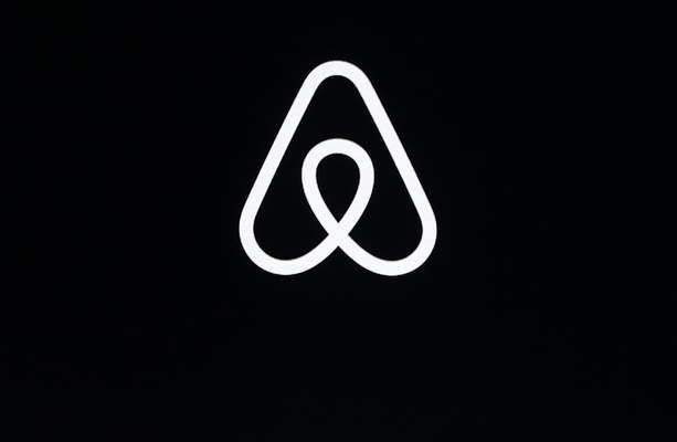 FILE - This Feb. 22, 2018, file photo shows an Airbnb logo during an event in San Francisco. A lucky few will be able to live the adventures of Phileas Fogg from Jules Vernes' classic Around the World in 80 Days. (AP Photo/Eric Risberg, File)