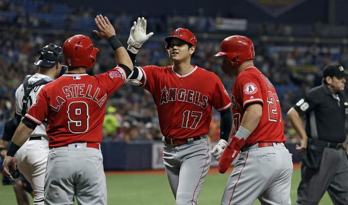 Associated Press The Angels' Shohei Ohtani, center, is greeted at home by Tommy La Stella and Mike Trout after hitting a three-run home run Thursday.