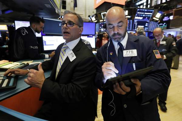 Associated Press: In this June 6, 2019, file photo specialist Anthony Rinaldi, left, and trader Fred DeMarco work on the floor of the New York Stock Exchange.