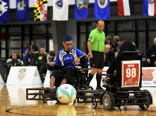 Katie Fyfe | The Journal Gazette  Vincent Lane with Team Force ASPO hits the ball while the Tidewater Piranhas' Nikki Dwyer tries to defend him during the 2019 Power Soccer Conference Cup Series at Turnstone Center for Children and Adults with Disabilities on Saturday.