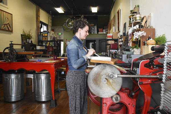 Michelle Davies | The Journal Gazette Julie Wall, owner of The Hedge, works on a custom printing order at Ginger, a C & P printing press built in 1897.