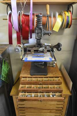 Michelle Davies | The Journal Gazette Various ribbons stored above a hot stamp press, along with the type used to print on them at The Hedge.