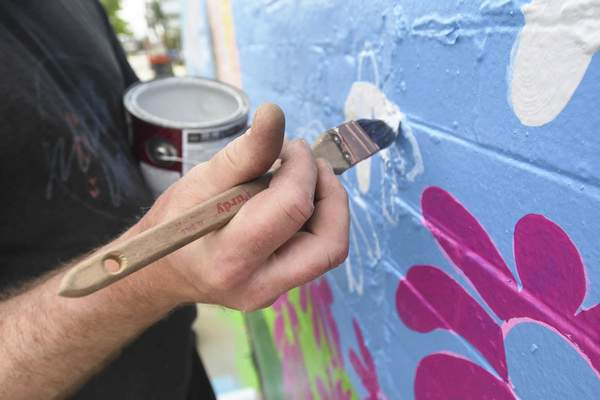Michelle Davies | The Journal Gazette Jerrod Tobias works on a mural at Wells and Fourth Street.