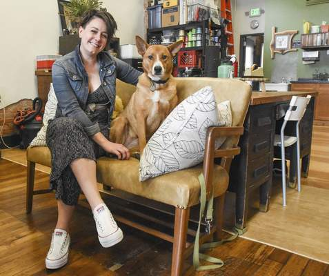 Michelle Davies | The Journal Gazette Julie Wall, owner of The Hedge, with her rescue dog, Lola, in her shop on Broadway.