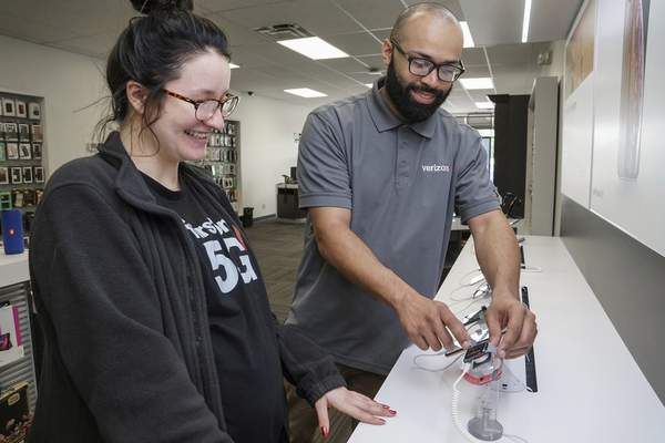 Mike Moore | The Journal Gazette Corey Worman demonstrates an Apple Watch for Claire Drummond at Fort Wayne's Wireless Zone on Illinois Road.