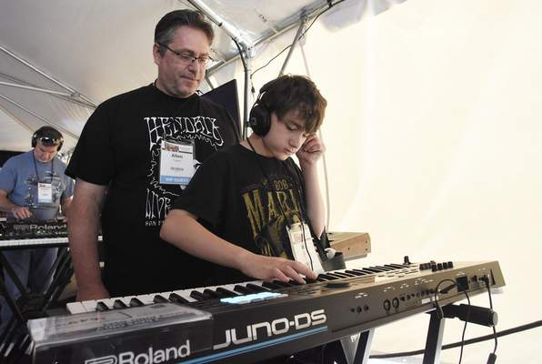 Rachel Von Stroup | The Journal Gazette  Allen Cypert, left, and son Max, 12, test out a Roland JUNO - DS61 synthesizer during GearFest at Sweetwater Sound on Saturday.