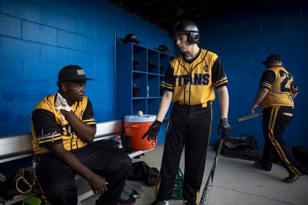 Jacob West talks to Rahsaan Washington in the dugout, after Rahsaan got hurt at first base against Summit Country Day School at Summit's Athletic Complex in Columbia Township, Ohio, Friday, April 26, 2019. (Meg Vogel/The Cincinnati Enquirer via AP)