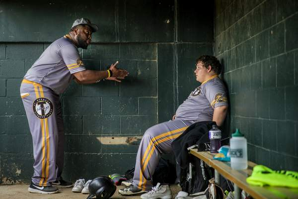 St. Bernard Titans coach Fred James instructs Dwayne Pot Pot Pottinger on how to keep his composure, after Pot Pot was taken out of the game for reacting to a teammate's error in the third inning against Lockland at Ross Park in St. Bernard, Ohio, Tuesday, April 23, 2019. James, the son of a preacher, prays a lot about his job. He's a baseball guy, a former minor leaguer, so he knew what he was getting into when he took over a team that had been outscored 571-76 the previous two seasons. What he didn't expect was that teaching baseball would be the least of his problems. (Meg Vogel/The Cincinnati Enquirer via AP)