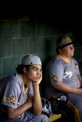 St. Bernard Titans baseball player Jaden Wood watches from the dugout during a game against Lockland in St. Bernard, Ohio, Tuesday, April 23, 2019. At St. Bernard, the baseball program's annual budget is $1,500. There is no junior varsity or freshman team. There is no middle school program. Some kids don't play organized ball until they put on a Titans' uniform. (Meg Vogel/The Cincinnati Enquirer via AP)