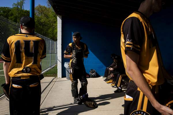 St. Bernard Titans' Jaden Wood, center waits to take the field in his catcher equipment in the first inning of a baseball game against Summit Country Day School in Cincinnati, Ohio, Friday, April 26, 2019. (Meg Vogel/The Cincinnati Enquirer via AP)