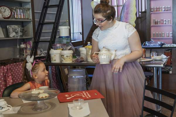 Mike Moore | The Journal Gazette  Dressed like a fairy, Hannah Stucky serves fairy-frizzle tea and peanut-butter and jelly sandwiches to guests during a fairy tea party at the WhatchamaCAKES bakery in Kendallville, Indiana during the Fairy, Gnome and Troll Festival on Saturday 05.18.19