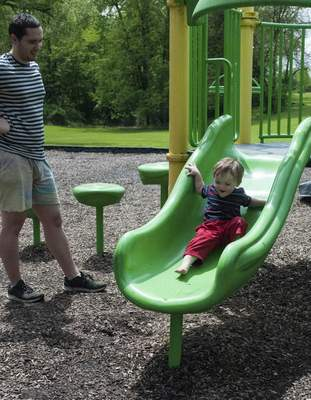 Terri Richardson  The Journal Gazette  Cole Bear of Columbia City watches his son, 1-year-old Isaiah, go down the slide at Morsche's Park. The park is a go-to place for residents.